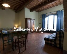 Otra vista del apartamento Petrarca, con la cama al fondo, el sofá cama y la entrada.