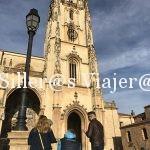 Grupo de 3 personas, una de ellas usuario de silla de ruedas, admiran la fachada de la catedral.