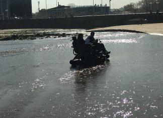Kity y Diana pasean por la orilla del mar con las sillas todoterreno
