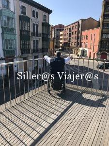 Kity, usuario de silla de ruedas observa la parte antigua de Avilés sobre una pasarela accesible.