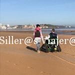 IZaskun y Kity pasean de la mano por la playa. Kity va en una silla de ruedas todoterreno
