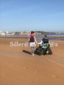 Usuario de silla de ruedas pasea de la mano de su pareja en la playa