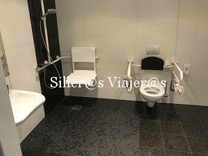 Indooro alzado con barras amabos lados y ducha a cota cero con asiento y barras de apoyo